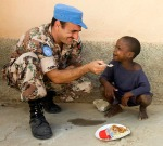 A Jordanian UN peacekeeper plays with a child during mealtime at the National School. (UN photo)