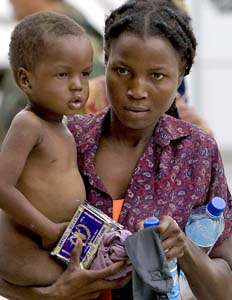 A woman and a child receive emergency rations in the aftermath of hurricane Ike last year in Gonaives, Haiti. (UN Photo/Logan Abassi)